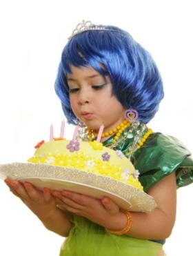 Una niña soplando las velas de su tarta de cumpleaños