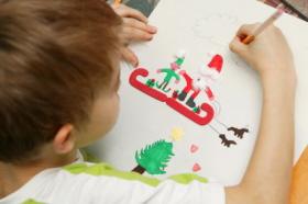 Un niño realiza un dibujo de Navidad