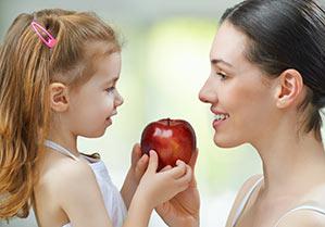 Encontrar niñera, canguro dando manzana a niña