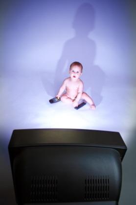 Un bebé mira la televisión sin la compañía de sus padres